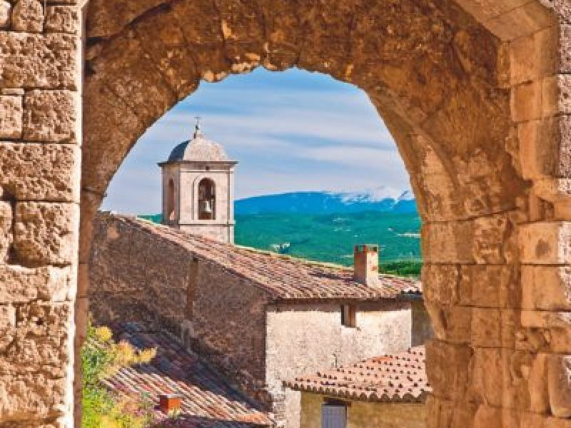 BD0X36 Church bell-tower through Medieval stone gate with Mont Ventoux beyond, Lacoste, Provence, France